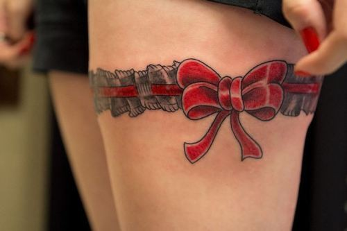 Red bow garter tattoo on upper leg