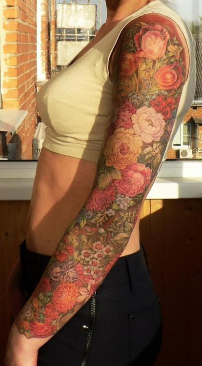 Full sleeve tattoo of multi colored flowers on girl