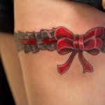 Red bow garter tattoo on upper leg
