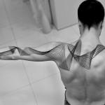 Chaim Machlev back and arm tattoo